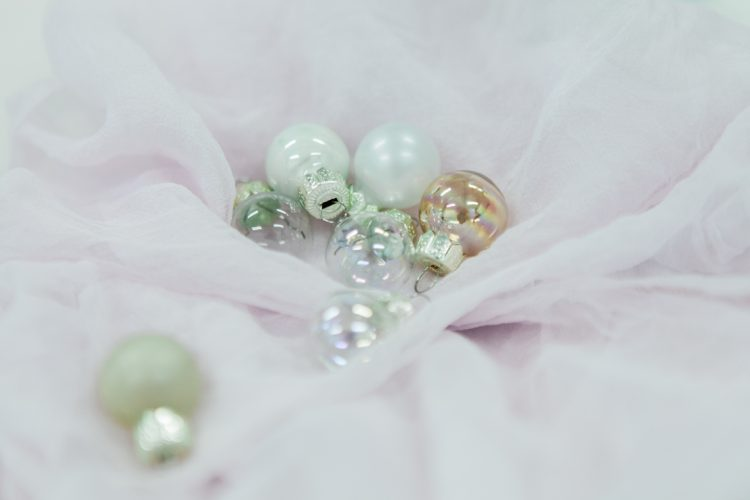 collection of Christmas baubles in metallics on a pink silk runner