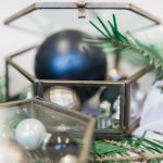 black and gold chirstmas baubles encased in hexagonal glass trinket boxes