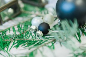 black and white christmas baubles on fir tree branches
