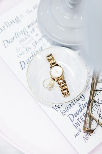 white ring dish with watch and glasses
