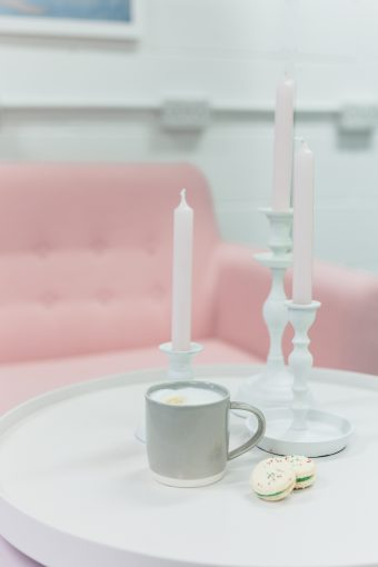 scandi style tables with white candle stick holders in various heights and blush pink tapered candles