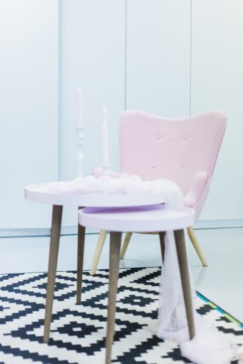 scandi style tables with white candle stick holders in various heights and blush pink tapered candles and modern pink armchair at the BLOVED HIVE studio space in Lodon