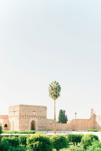 architecture of building in Morocco with cream brickwork and tall palm trees