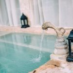 luxe spalsh pool turquoise water with brass fish shaped tap