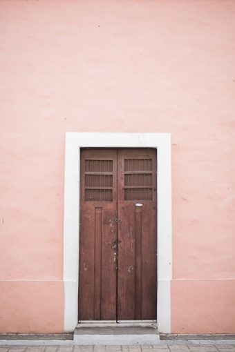 pink wall with wooden door