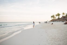 woman walking along a serene sand beach in Mexico