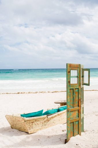 Tulum Mexico beach decor details with boat seating area and rustic doors