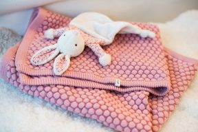 pretty pink baby blanket with honeycomb texture and a toy bunny