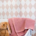 pretty pink baby blanket with honeycomb texture draped over a stylish crib