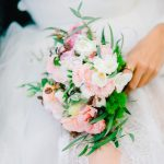bride holding wedding bouquet against tulle skirt