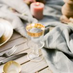 table setting with wine glasses with a gold rim