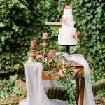 small dessert table display with an ivy wall backdrop
