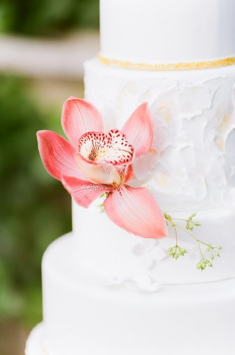 wedding cake topped with pink orchids