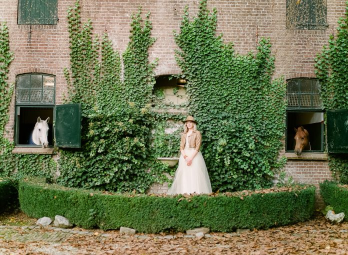 bridal look wearing a western hat against a wall backdrop filled with ivy