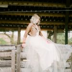 bride sat on a fence with a western style and wearing cowboy boots