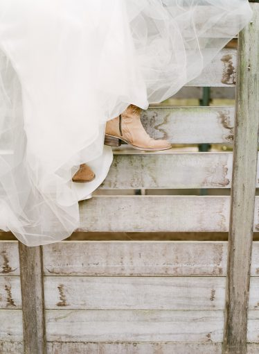 bride wearing cowboy boots peeping out from under her wedding dress