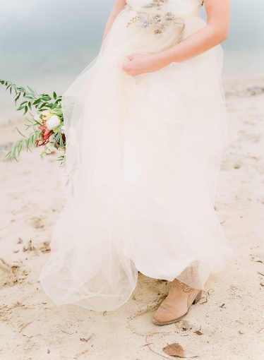 bride in the sand of the lake with cowboy boots peeping out of her dress