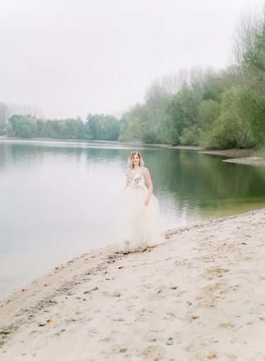 bridal portrait walking alone the edge of a lake