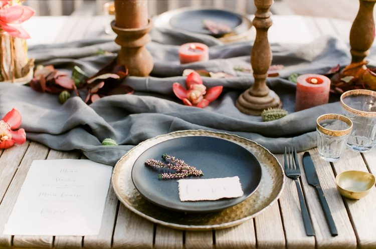 table setting with gold charger and matt black plate