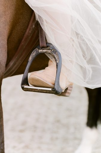 bride wearing western cowboy boots and horseriding