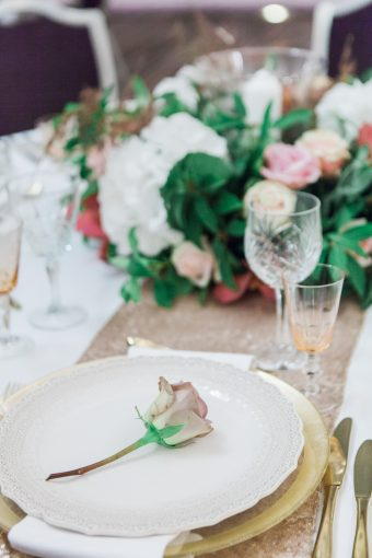 wedding table setting with gold charger plates and rose place setting