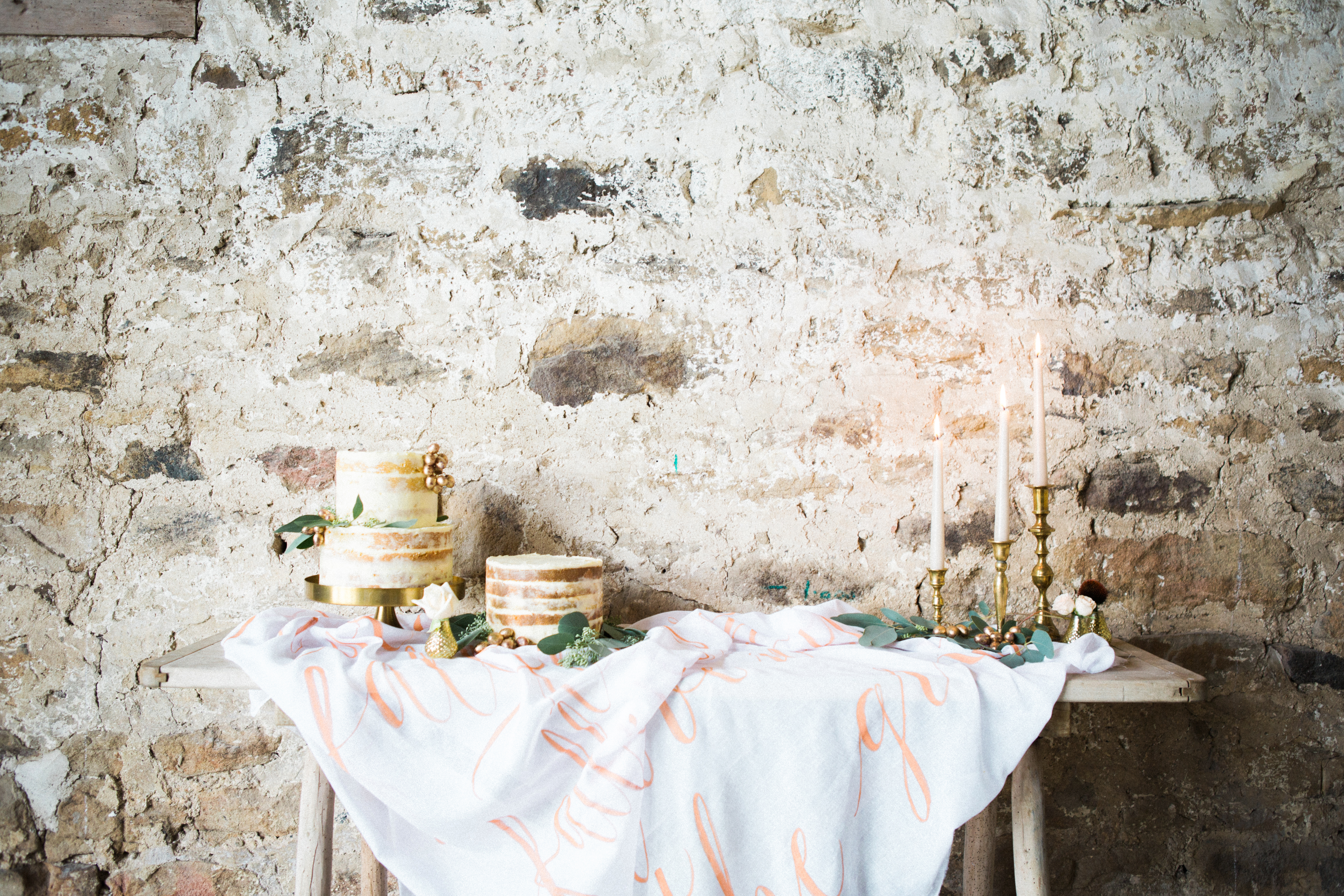 dessert table of wedding cakes against a barn brick wall with rustic taper candles