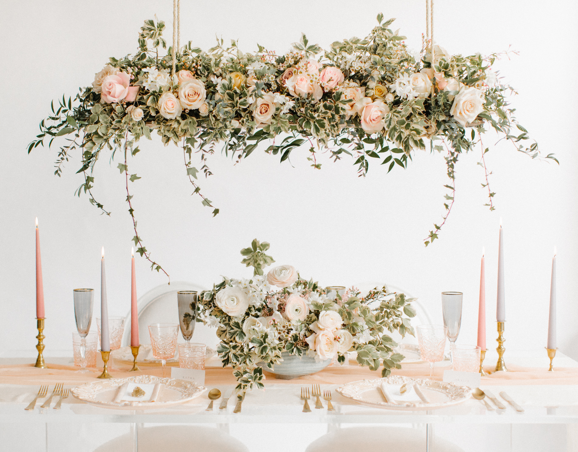 wedding table setting with hanging floral installation and colour palette of white peach pink and grey