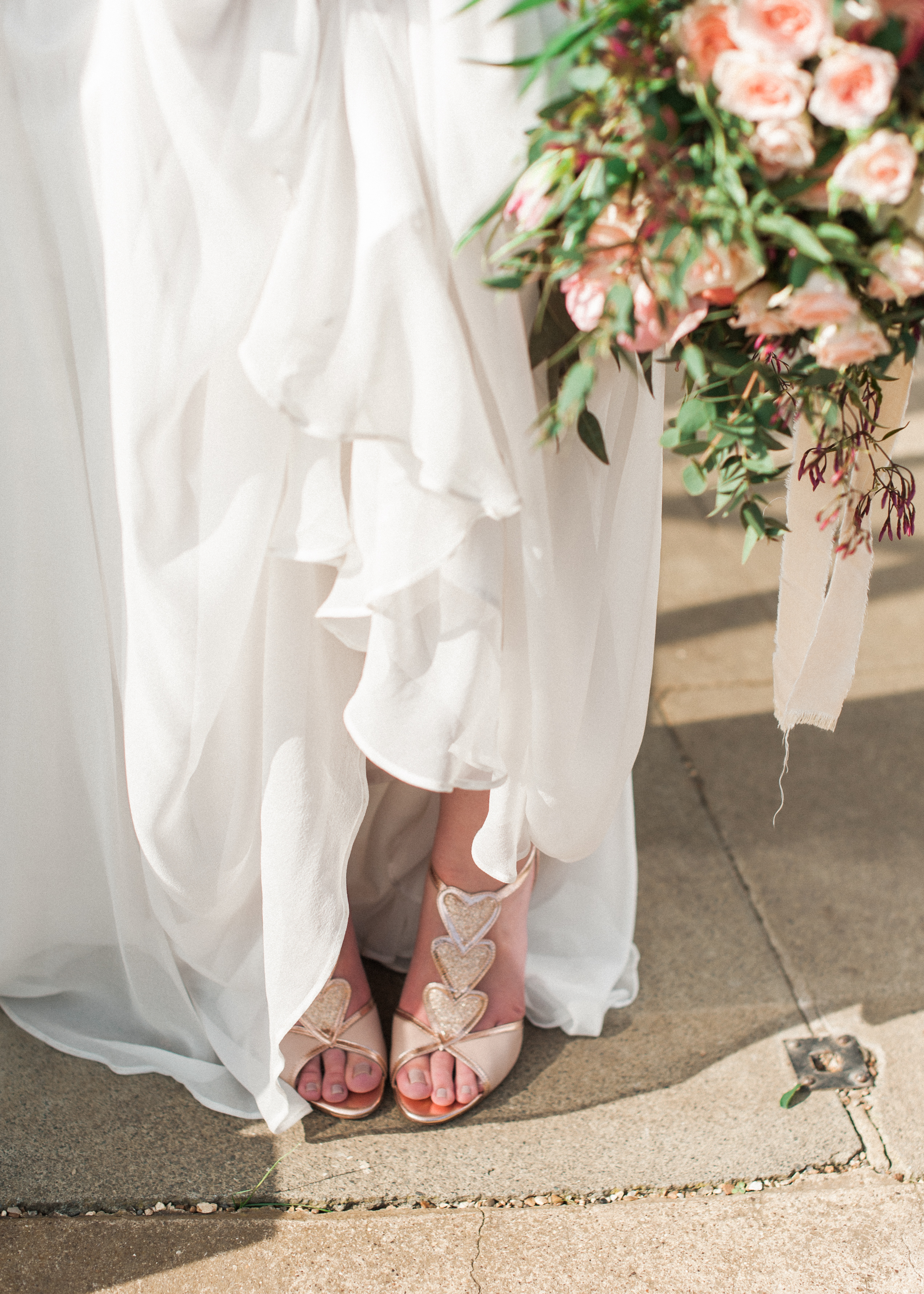 bridal details of silk wedding dress skirt, glittery shoes and bouquet of flowers