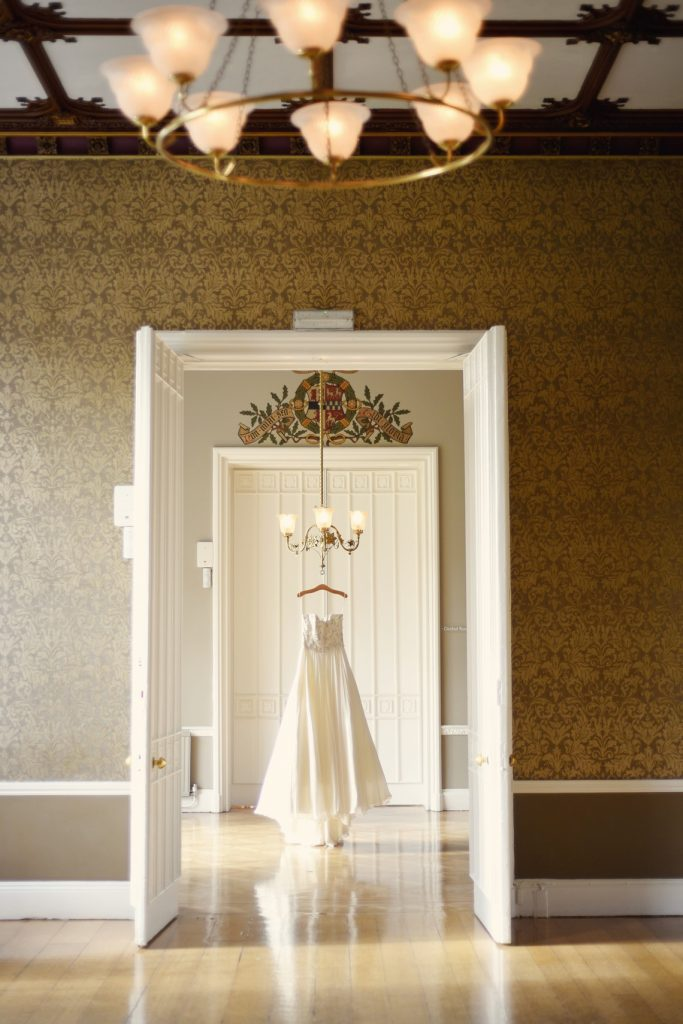 doorways of nonsuch mansion with the wedding dress hanging from the chandelier
