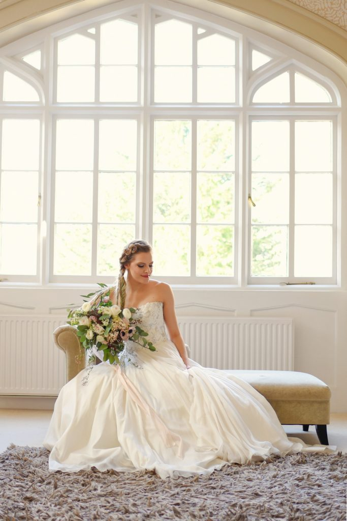 bridal portrait seated in front of huge windows of the mansion