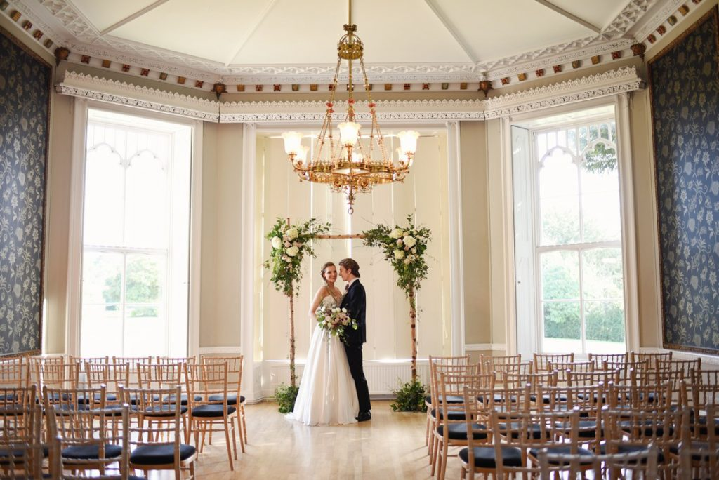 nonsuch mansion ceremony room with floral arch and bamboo chairs