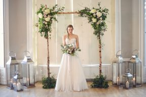 bride stood under the floral ceremony arch