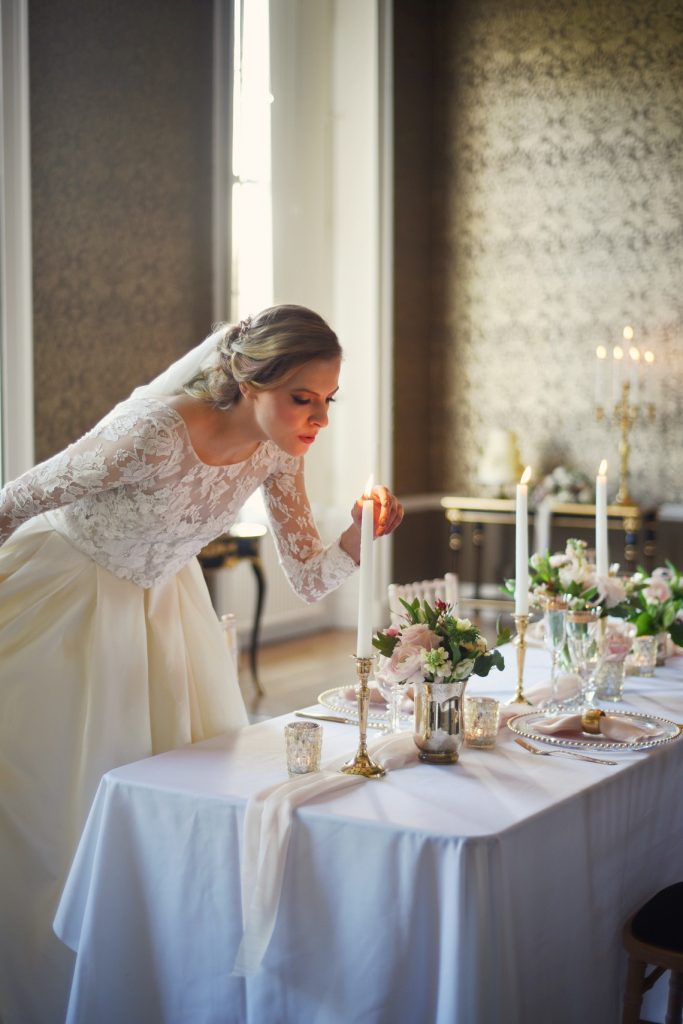 bride blows out taper candles