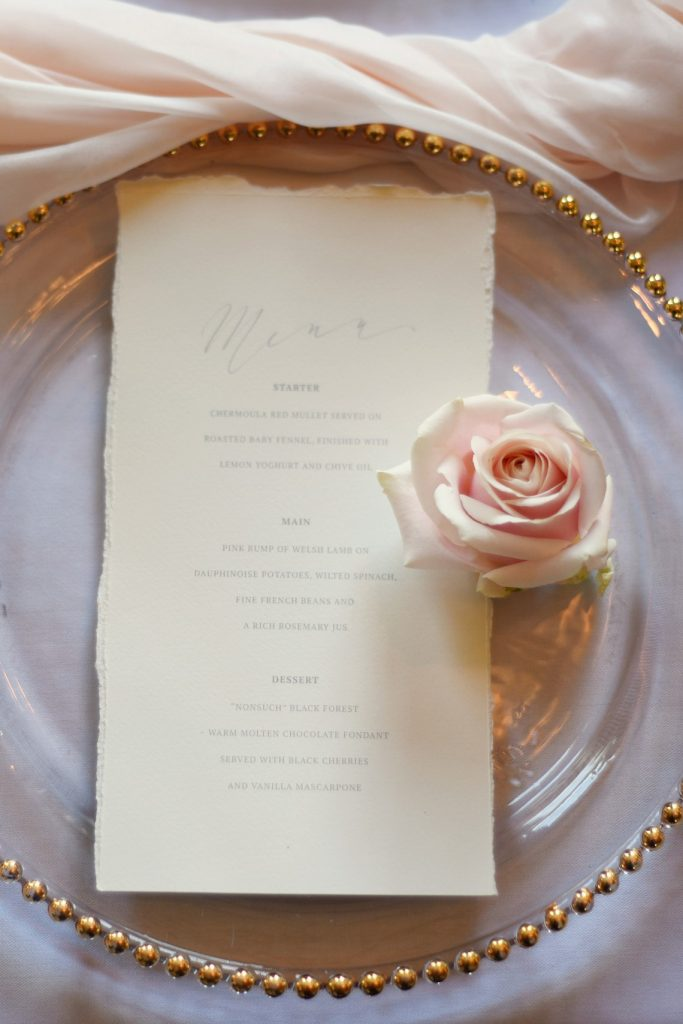 glass charger plate with menu design and pink rose