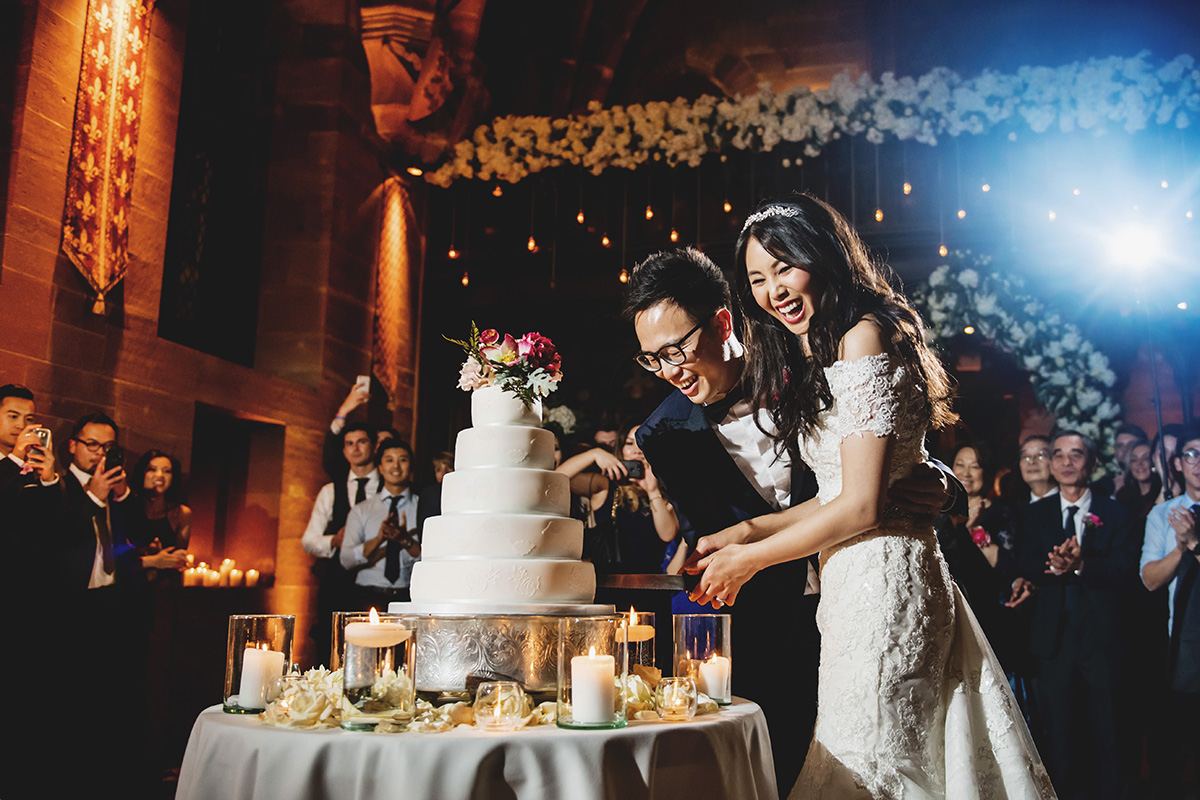 bride and groom smile and laugh with joy as cutting their luxury wedding cake surrounded by candles