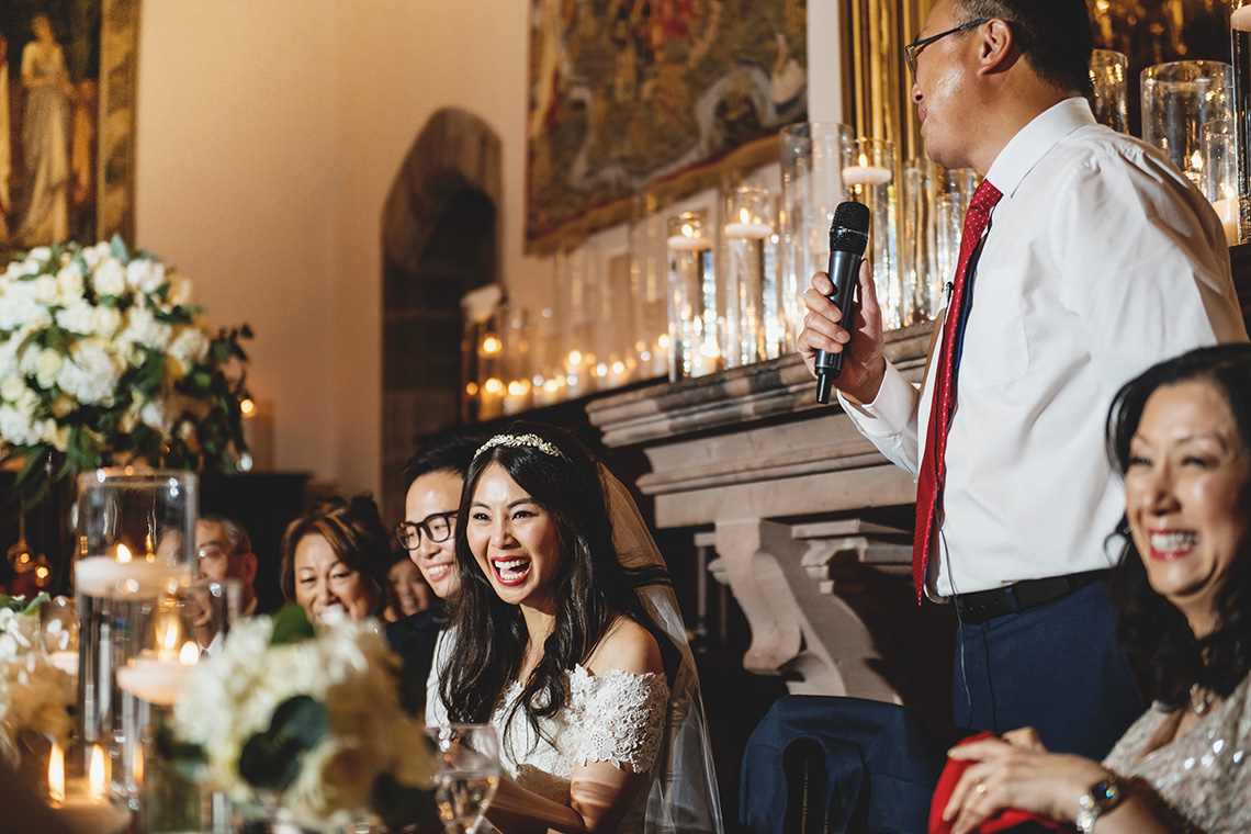 bride and groom laugh at the father's wedding speech