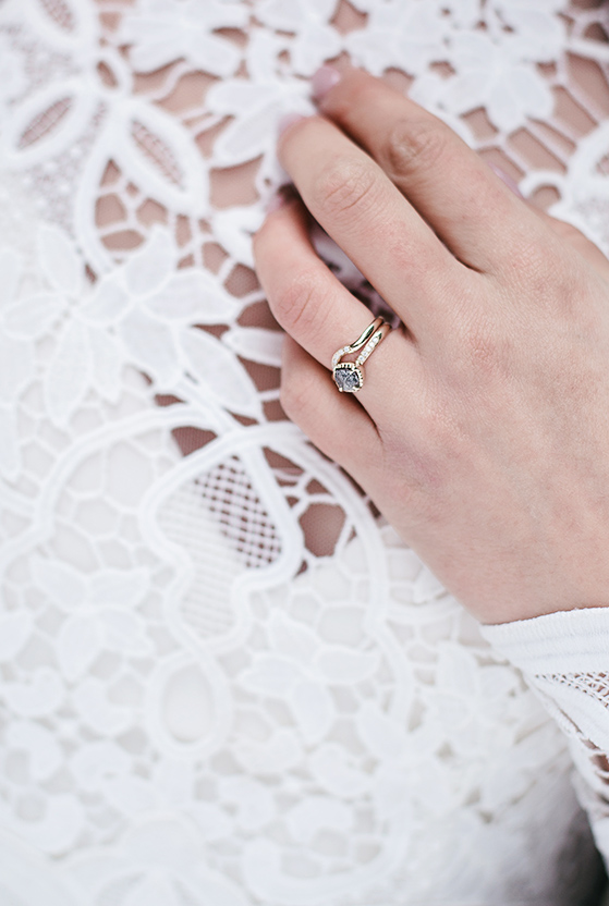 bride's lace dress and contemporary rings
