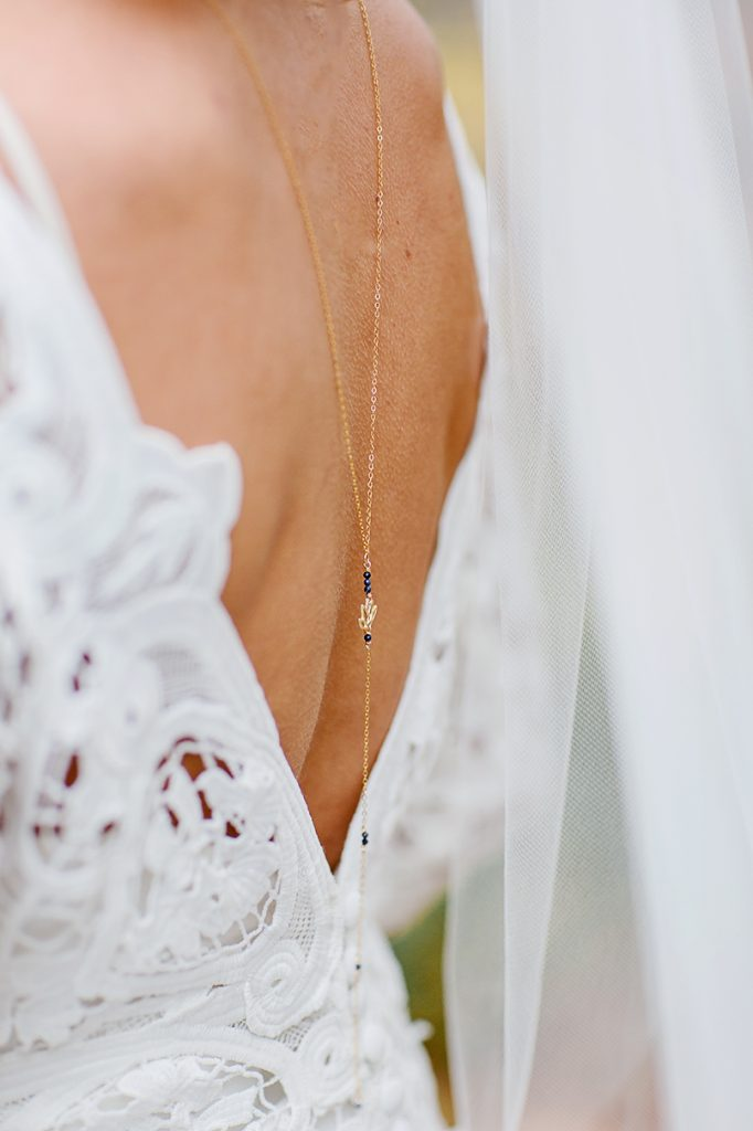 low back wedding dress details with long back necklace lariat