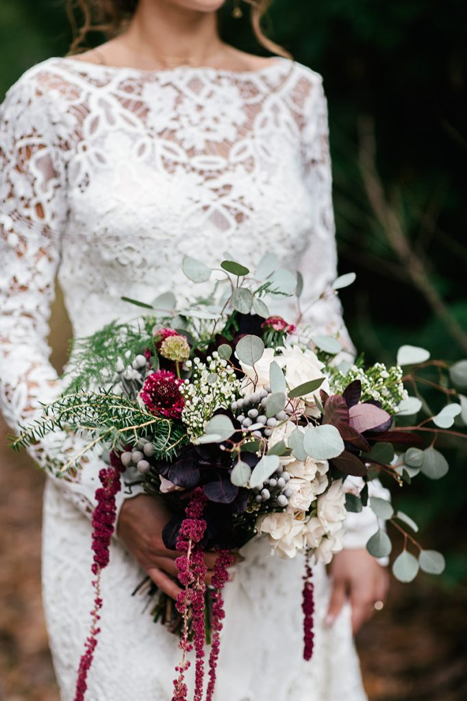 lace wedding dress and winter bridal bouquet of blue white and burgundy