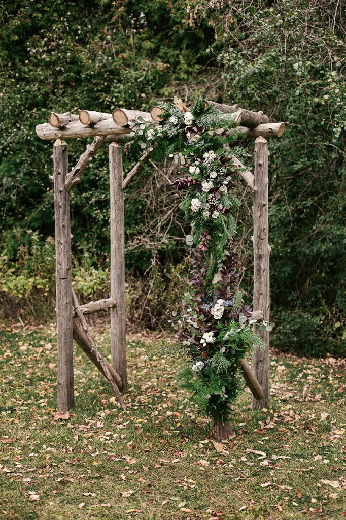 woodland wedding ceremony setting with arch covered in flowers