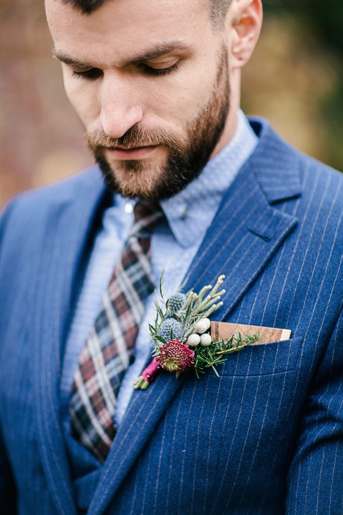 groom's navy three piece suit with check tie and pocket square