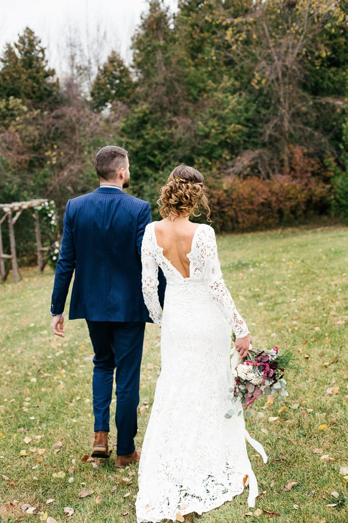 groom wearing navy suit and bride wearing crochet lace