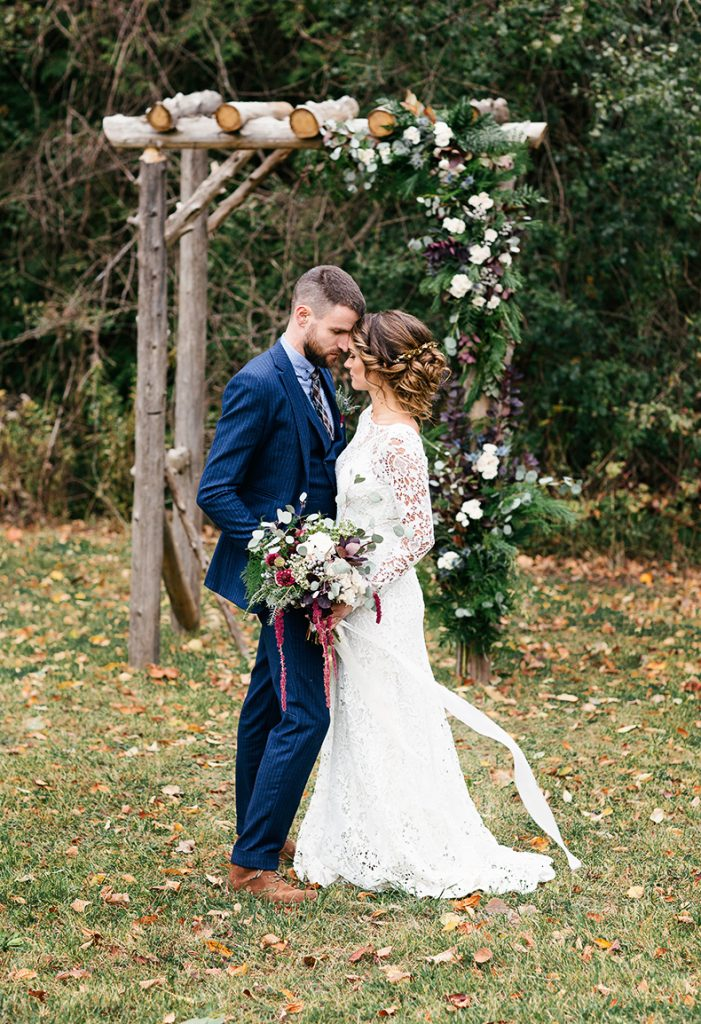 bride and groom with ceremony arch design covered in flowers
