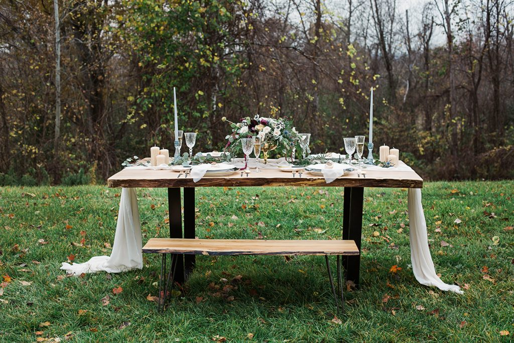 outdoor wedding table with silk runner taper candles and bench seating