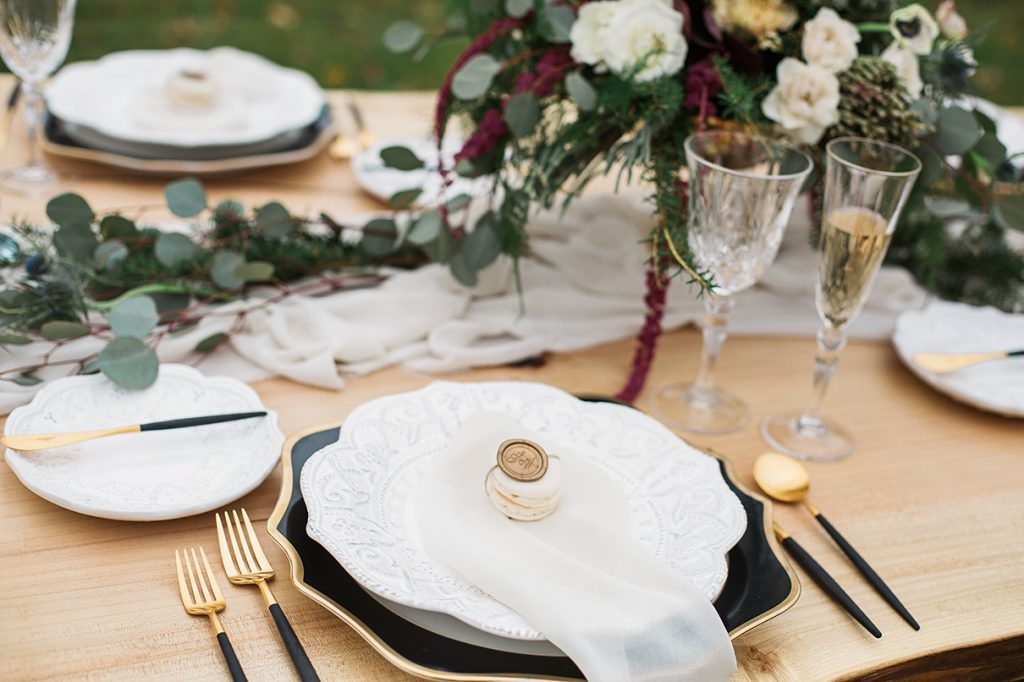 contemporary wedding table setting with black and white and gold