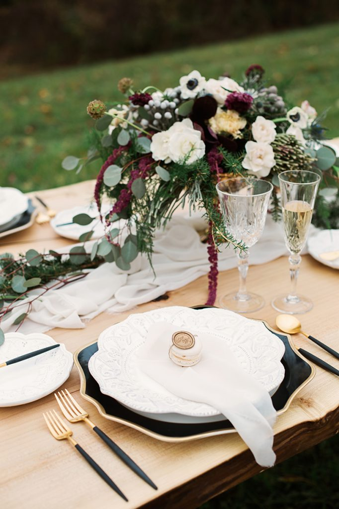 modern place setting with black white and gold plate and flatware