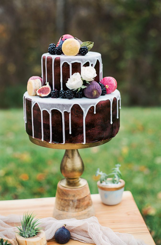 two layer chocolate wedding cake dripping with white and topped with fruit and figs