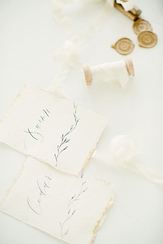 calligraphy place cards on handmade paper with silk ribbon spool