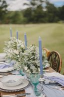 wedding table decor with silk runner and blue taper candles