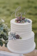 two tier wedding cake with love cake topper and succulents